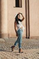 senhora indiana em roupa de verão casual contra edifício antigo.