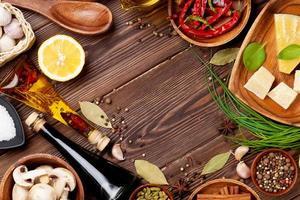 várias especiarias e condimentos numa superfície de madeira foto