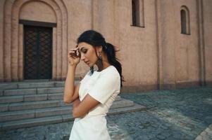 senhora de vestido contra o edifício antigo, com olhar pensativo