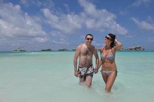 feliz casal jovem se divertir na praia foto