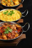 uma refeição de curry indiano preparada em frigideiras
