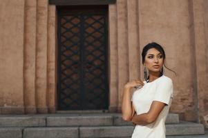 senhora indiana de vestido contra o edifício antigo, com olhar pensativo