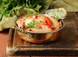 camarão frito com pimenta em uma panela de cobre, estilo indiano foto