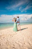 casal de férias andando na praia tropical Maldivas.