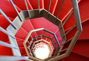 escada em espiral moderna com tapete vermelho