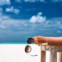 mulher na praia segurando óculos de sol foto