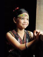 jovem kadazandusun em traje tradicional de pé junto à janela