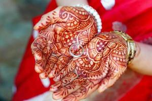 mãos pintadas com henna segura o anel de casamento foto