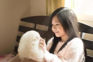 pouco asiático brincando com filhotes de husky siberiano foto