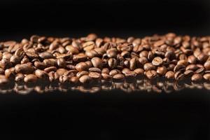 linha de grãos de café torrados aromáticos colocados sobre fundo preto. foto
