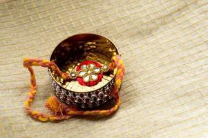 rakhi mantido em uma caixa dourada decorada foto