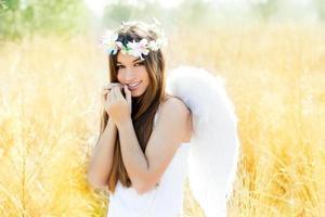 menina anjo em campo dourado com asas de penas brancas foto
