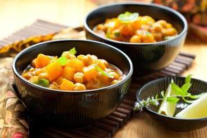três tigelas pretas cheias de curry de abóbora e acompanhamentos foto