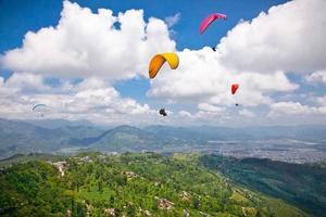 parapente voando contra o Himalaia, nepal.