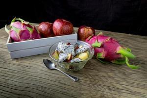 salada de frutas em uma tigela em cima da mesa de madeira foto