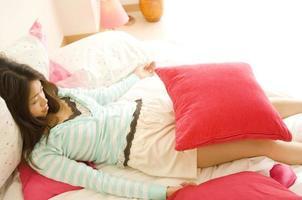 mulher japonesa na casa dos vinte, deitada com almofada foto