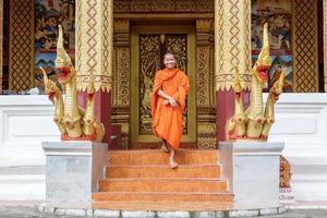 jovem monge budista andando na frente do mosteiro foto