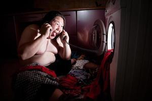 homem gordo asiático perto da máquina de lavar roupa