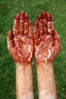 mãos de mulher com design de henna foto