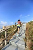 corredor de trilha de mulher jovem fitness subindo as escadas da montanha foto