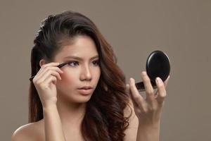 feminino asiático aplicando delineador foto