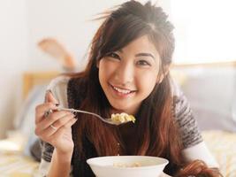 feliz menina asiática comendo sopa de macarrão de galinha foto