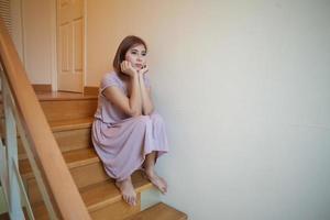 jovem mulher asiática senta-se sozinha na escada foto