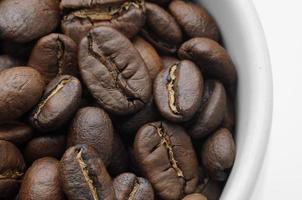 assar grãos de café orgânicos na caneca branca foto