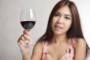 linda mulher asiática segurar o copo de vinho tinto foto
