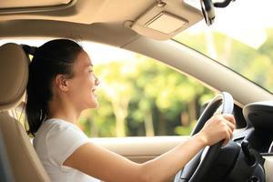 motorista mulher feliz dirigindo seu carro foto