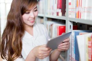 aluna linda asiática usando tablet na biblioteca