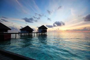 casas maldivas no nascer do sol