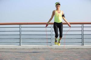 mulher jovem fitness pulando corda na beira-mar foto