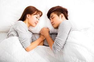 casal adorável jovem feliz, deitado em uma cama foto
