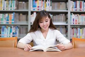 bela aluna asiática ler livro na biblioteca foto