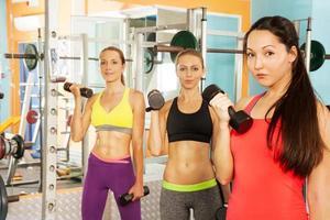 três jovens mulheres no clube de fitness foto