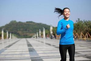 mulher asiática de esportes correndo no parque da cidade foto