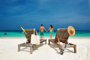 casal de verde em uma praia nas Maldivas