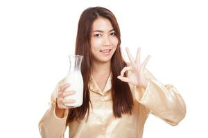 feliz mulher asiática mostra ok beber leite de manhã foto