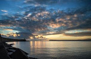 lindo céu vibrante do nascer do sol sobre o oceano calmo com farol foto