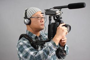homem com câmera hd slr e equipamento de áudio