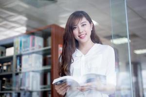 aluna linda asiática segurando o livro no retrato da biblioteca foto