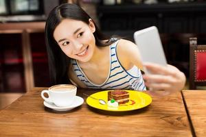 garota em mensagens de texto de loja de café em smartphone foto