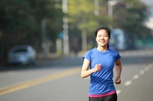 ajuste esportes mulher correndo na estrada de asfalto foto