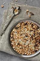 arroz multigrain cru na placa de metal no fundo de madeira foto