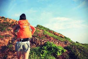 mochileiro de jovem mulher subindo ao pico da montanha foto