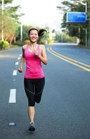 mulher asiática de esportes correndo na estrada da cidade foto