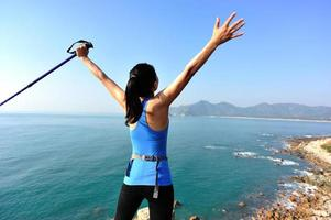 caminhadas mulher levantou os braços para o mar azul foto