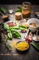 seleção oriental de ervas e especiarias na mesa da cozinha rústica foto