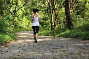 mulher jovem fitness correndo na trilha de pedra da floresta foto